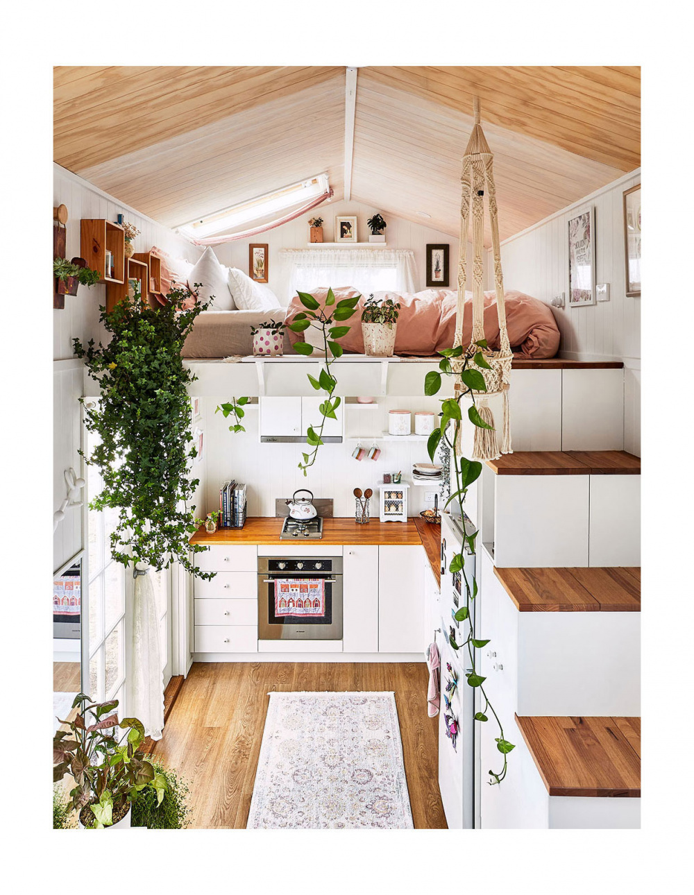 A beautiful, salmon-hued tiny home on wheels with upstairs living